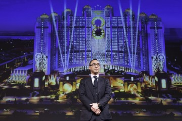 Lawrence Ho in front of artist rendition of Studio City in Cotai, Macau